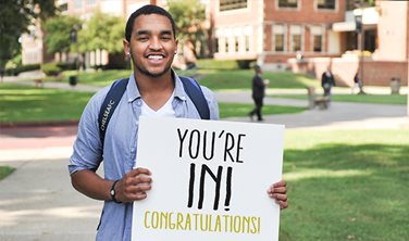Smiling student holding a sign saying You're In. Congratulations.